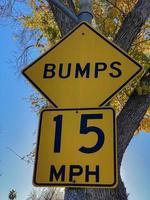 Señal de tráfico de advertencia de golpes amarillos en un árbol foto