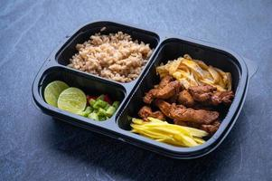 Sectioned plastic food container with meat, noodles, and rice