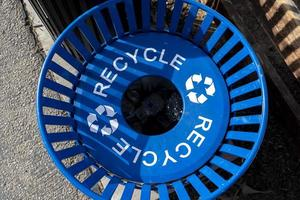 A blue metal recycles bin from the top in the park