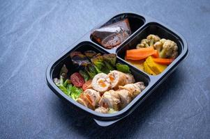 Sectioned plastic food container with salad, sliced meat, and vegetables