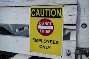 Yellow employees only sign on a wooden door