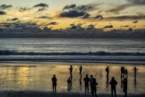 Silhouette of people by the blue and yellow sunset at the beach photo