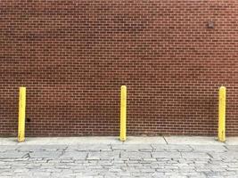 Pared de ladrillo con protectores de metal amarillo en la acera foto