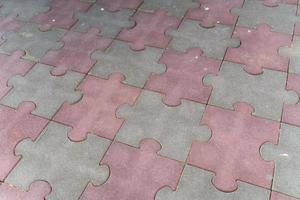 Worn grey and pink puzzle shape paving stones photo