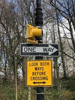 Look Both Ways Before Crossing and One Way traffic sign on a pole photo