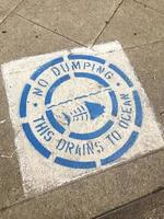 No Dumping Drains to the Ocean sign on the floor