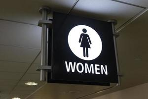 A women's bathroom sign at an airport