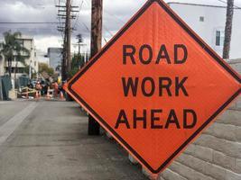 Signo de trabajo en la carretera naranja adelante con los trabajadores en el fondo borroso