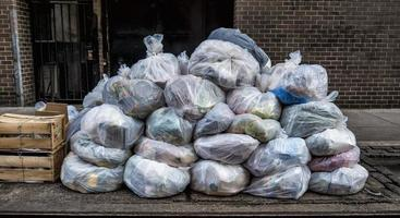 montones translúcidos de bolsas de basura en la acera foto