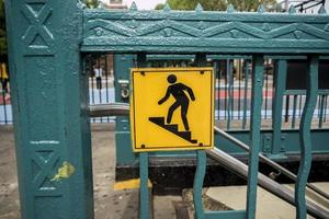 Subway stairs sign on a metal barrier photo