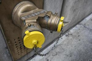 Yellow Siamese connection pipe on a wall