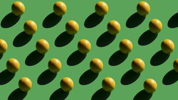 Lemons on a green background with shadows on sunlight