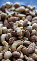 Pile of mixed nuts on a blue background