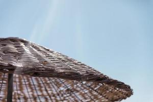 Straw beach umbrella on a sunny day