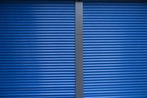 Blue metal store doors with a gray frame