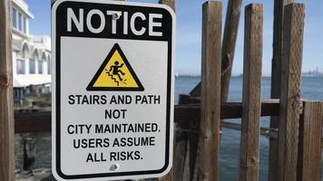 Escaleras y ruta no mantenida por la ciudad signo de aviso de texto en una valla de madera foto