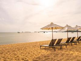 Umbrellas and sunbathing beds on the tropical beach photo