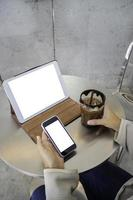 Person sitting at coffee shop with two blank mockup screens photo