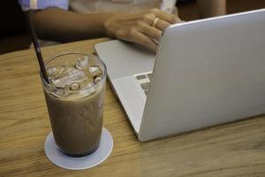 Bebida de café helado en la mesa de madera con portátil foto