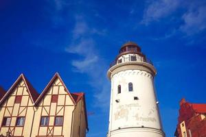 Species Tower Lighthouse between two buildings with cloudy blue sky in Kaliningrad, Russia