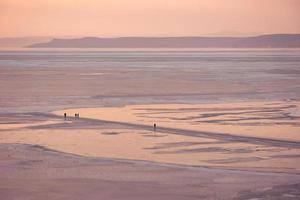 Siluetas de personas caminando sobre hielo en la bahía de Amur en Vladivostok, Rusia foto