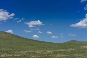 Landscape with fields and hills and cloudy blue sky