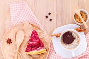 Raspberry cake with cup of coffee on wooden background
