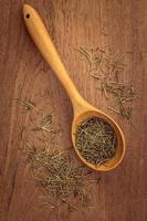 Dried rosemary leaves in wooden spoon photo