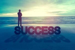 silueta de un hombre de pie en el océano con la palabra éxito foto