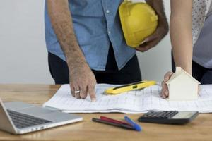 Engineer discussing blue prints on working table photo