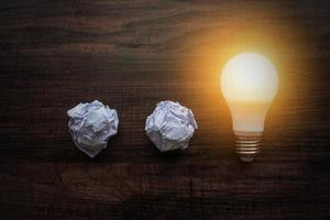 Ideas concept, lightbulb with crumbled paper photo