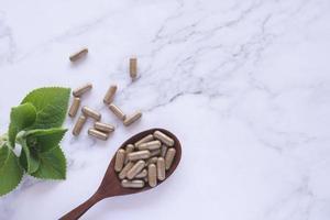 Medicina herbaria en cápsulas en cuchara de madera foto