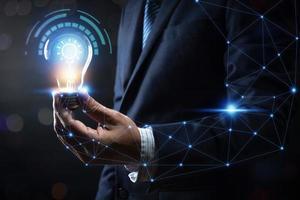 Business man holding a lightbulb photo
