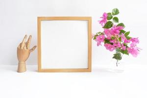Blank wooden frame with flowers in a vase photo
