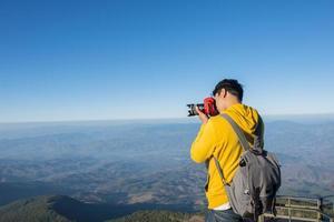 Fotógrafo tomando fotos en la cima de una montaña en Tailandia