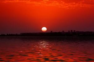 Sunset over city skyline by body of water photo