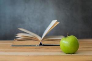 Manzana verde con libro abierto sobre mesa de madera foto