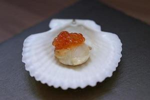 Red caviar on a scallop fillet on a white porcelain shell plate on table photo
