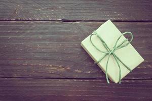 Caja de regalo marrón sobre fondo de madera foto