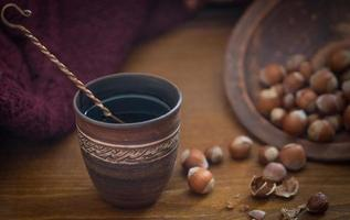Ornate ceramic cup next to hazelnuts on table