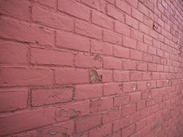 pared de ladrillo rojo con la pintura descascarada