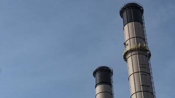 Metal chimney of a factory on a blue sky photo