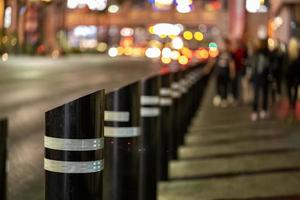 Security barriers on the sidewalk with people in the blurry background photo