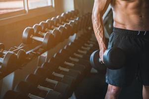 Man holding a dumbbell in a gym with row of dumbbells in the background