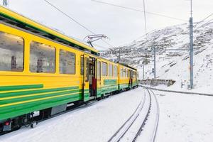Train cars on the Jungfrau Railway against snowy mountains in Switzerland photo