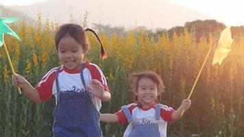 Happy little children playing with windmill in field of flowers