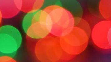 Abstract defocused Christmas lights on dark background.