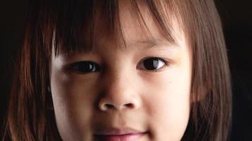 Retrato de primer plano de la cara de la niña linda mirando a la cámara video