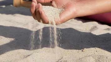 Close up of hand pouring sand running through fingers slow motion video