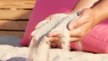 Gros plan de la main de la femme verser du sable à travers les doigts au ralenti